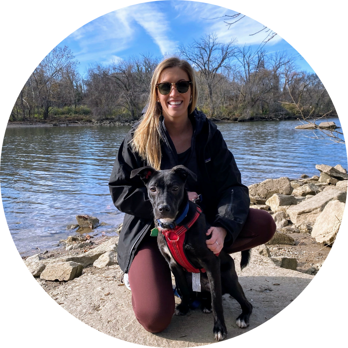 woman by water with dog