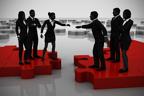 Two teams of successful executives merging on a jigsaw puzzle showing a partnership.